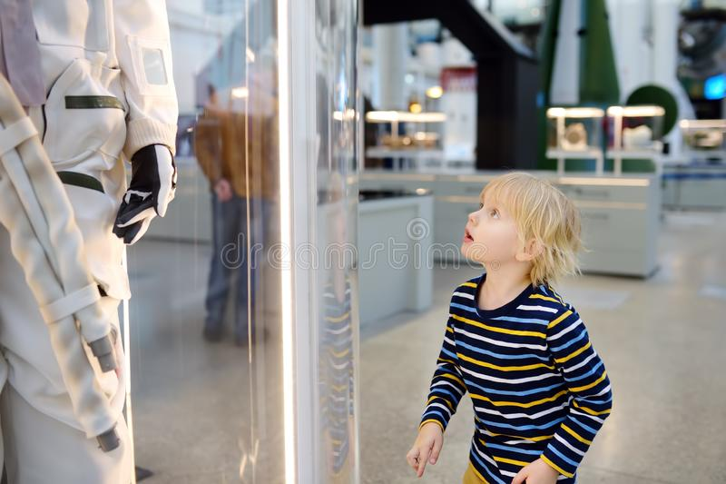 Little caucasian boy looking astronaut space suit in museum. Little blond caucasian boy looking astronaut space suit in museum. Education and entertainment for stock photo