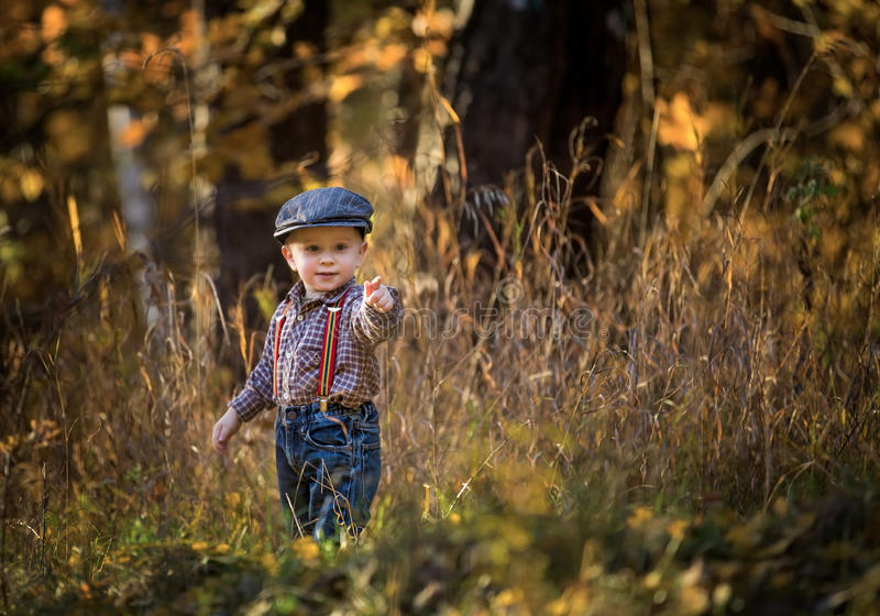 Little caucasian boy playing in springtime landscape stock photo