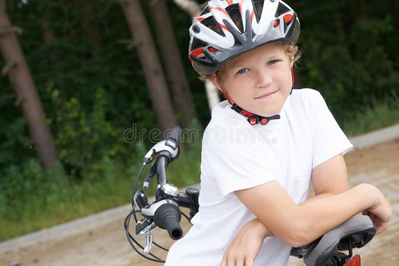 Little Caucasian boy in protective helmet stands leaning on the bike posing for the camera. Teenager ready to ride. Small Caucasian boy in protective helmet royalty free stock photos