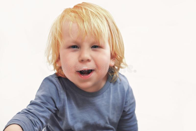 A child of three years old looks at the camera and laughs, white background, close-up royalty free stock images
