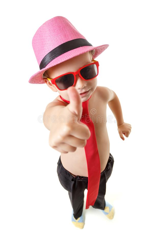 Little boy in tie, sunglasses, and hat is dancing, isolated on white. Little cute cheerful kid is dancing on white background. royalty free stock images