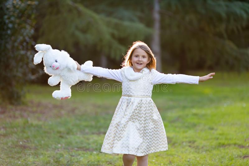 Little Caucasian girl with blond hair in white and golden festive dress running happily toward the camera, laughing, holding big p stock photo