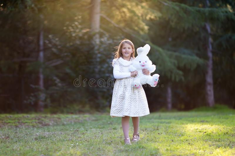 Little Caucasian girl with blond hair in white and golden festive dress walking toward the camera, smiling, holding big plush bunn royalty free stock image