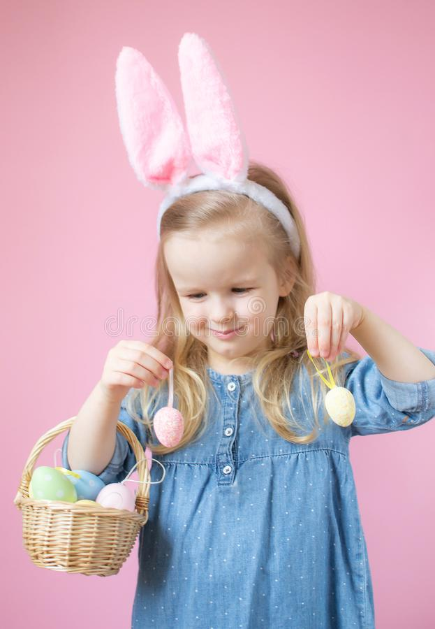 Little caucasian girl with bunny ears standing with wooden basket full of colorful Easter eggs royalty free stock image