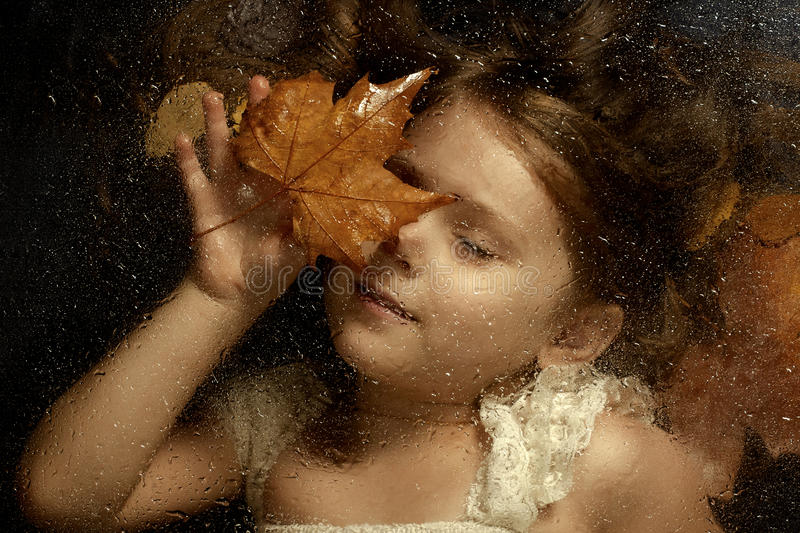 Little caucasian girl, close up portrait across a water drops. On glass, with autumn leaves in background. Emotional portrait, autumn concept stock photography