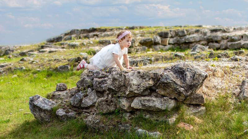 Little Caucasian girl in a dress scrambles on old outdoor ruins stones. Beautiful elegant child walking in the summer beautiful royalty free stock photos