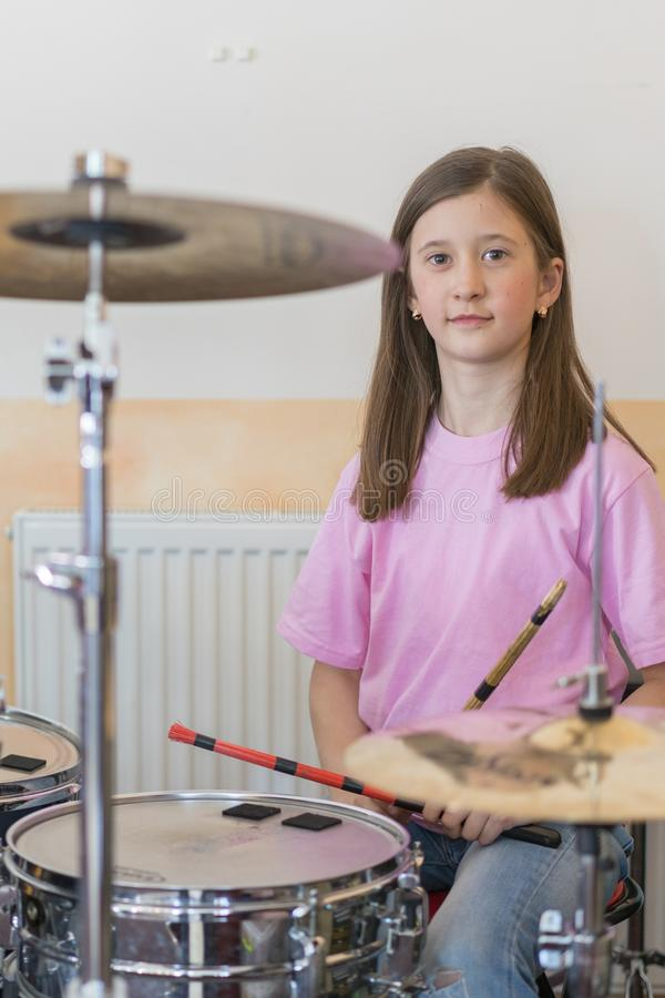 Little caucasian girl drummer playing the elettronic drum kit and shuoting. Teen girls are having fun playing drum sets in music stock photos