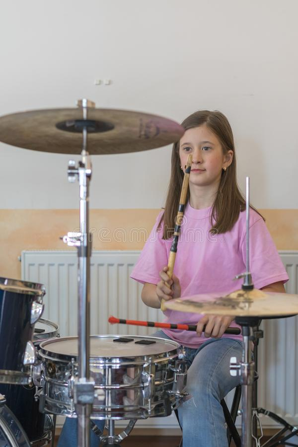 Little caucasian girl drummer playing the elettronic drum kit and shuoting. Teen girls are having fun playing drum sets in music stock photography