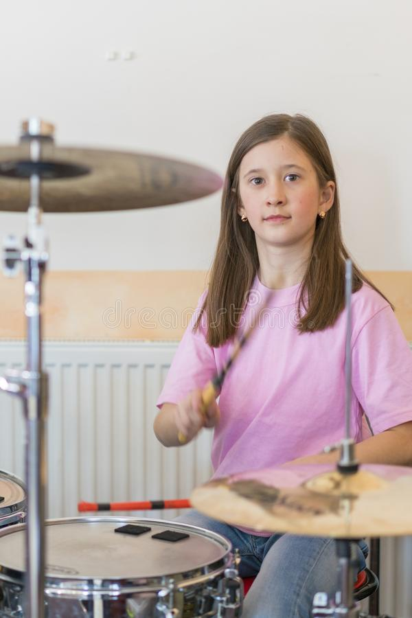 Little caucasian girl drummer playing the elettronic drum kit and shuoting. Teen girls are having fun playing drum sets in music royalty free stock photography