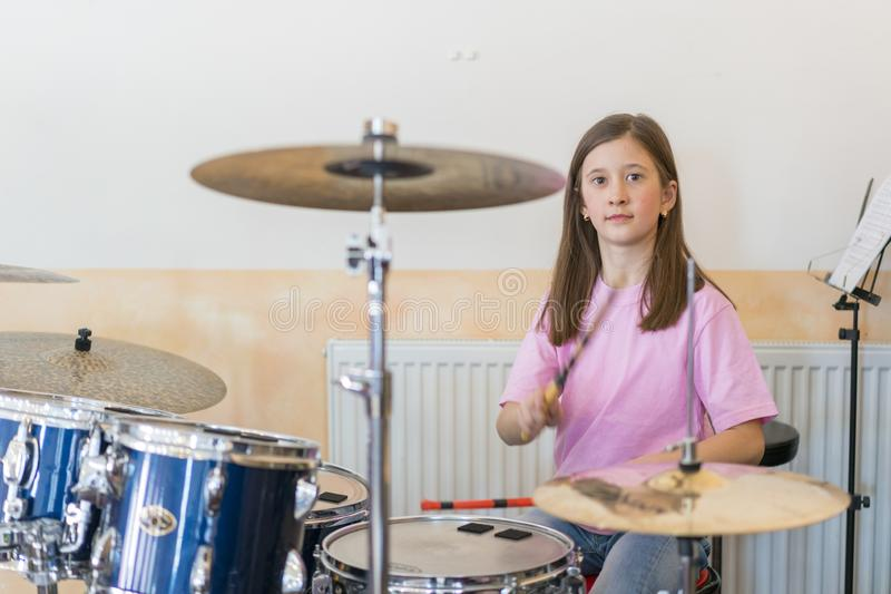 Little caucasian girl drummer playing the elettronic drum kit and shuoting. Teen girls are having fun playing drum sets royalty free stock photos
