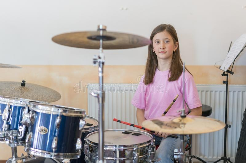 Little caucasian girl drummer playing the elettronic drum kit and shuoting. Teen girls are having fun playing drum sets in music royalty free stock images