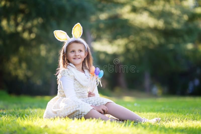 Little Caucasian girl in festive dress and bunny ears headband sitting on green grass and playing with Easter eggs stock photos