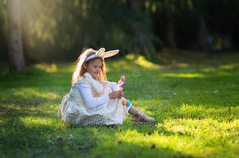 Little Caucasian girl in festive dress and bunny ears headband sitting on green grass and playing with Easter eggs royalty free stock photos