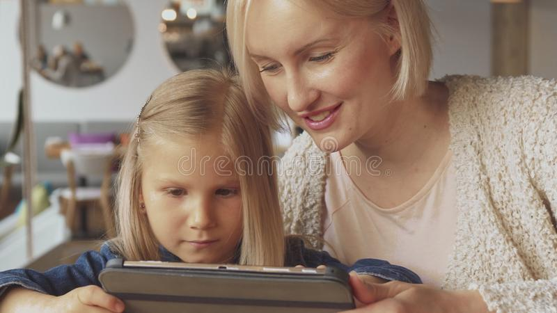 Little girl flips on tablet at the cafe stock photos