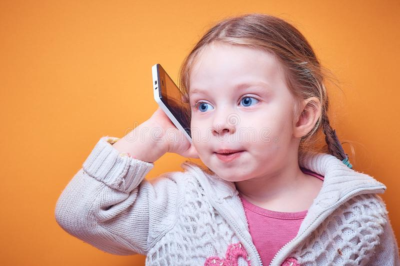 Little Caucasian girl with a phone in her hand on a colored background, a place for text royalty free stock image