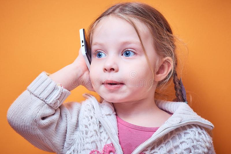 Little Caucasian girl with a phone in her hand on a colored background, a place for text stock images