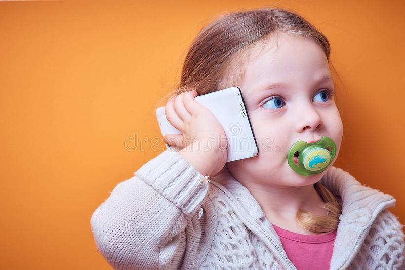 Little Caucasian girl with a phone in her hand on a colored background, a place for text royalty free stock photos
