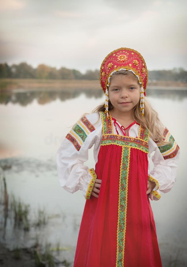 Little Caucasian girl in Russian national costume on blur natural landscape background royalty free stock photography