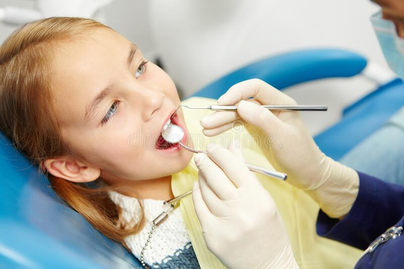 Little caucasian girl sitting in the chair on pediatric dentistry clinic. Early prevention, raising awareness, oral hygiene demonstration concept royalty free stock images