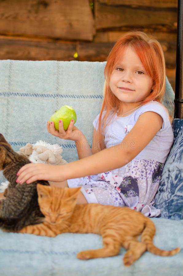 A little caucasian girl of six years old is sitting on a garden swing, playing with kittens and eating green apples. Happy. Carefree childhood in the village stock photo