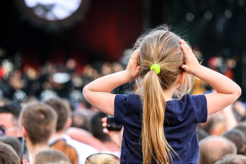 Little Caucasian girl on father`s shoulders watching the concert in the crowd stock photography