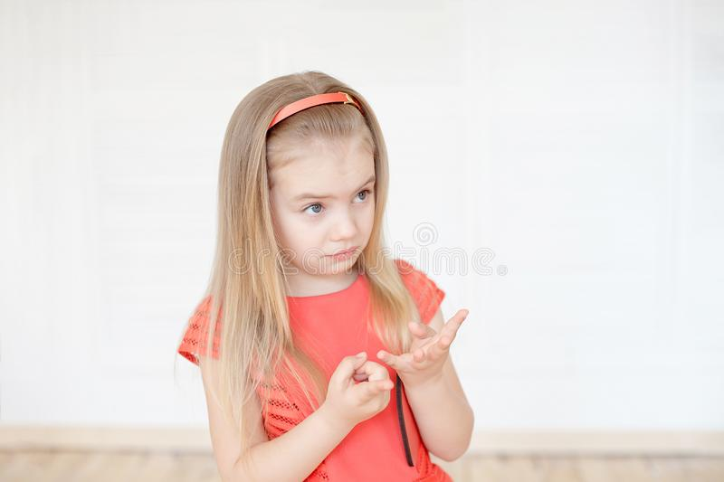 Little caucasian girl thoughtful counting her fingers indoors. royalty free stock image