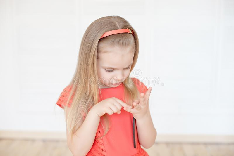 Little caucasian girl thoughtful counting her fingers indoors. stock image