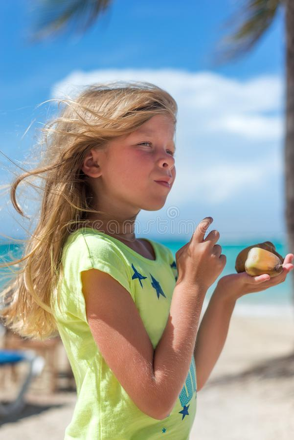 The little Caucasian girl on the tropical beach is holding nuts. Blue sky and palms are on the background royalty free stock photography