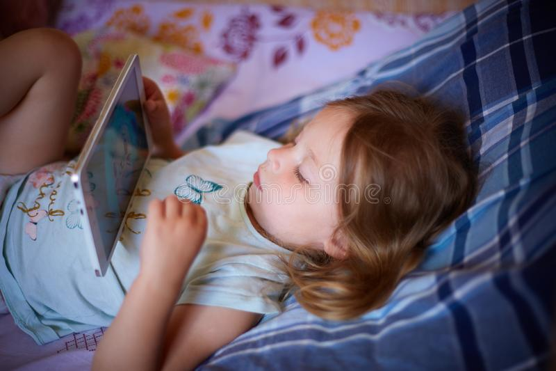Little Caucasian two-year-old girl lying on a plaid pillow and watching cartoons on a tablet computer. modern technology stock photography
