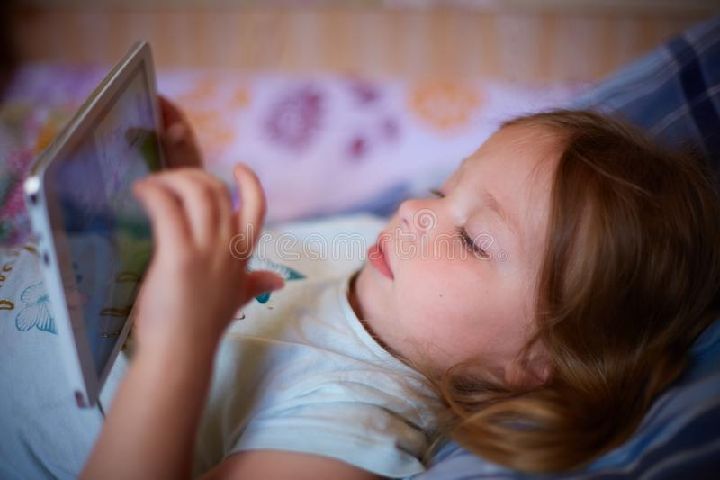 Little Caucasian two-year-old girl lying on a plaid pillow and watching cartoons on a tablet computer. modern technology stock photos