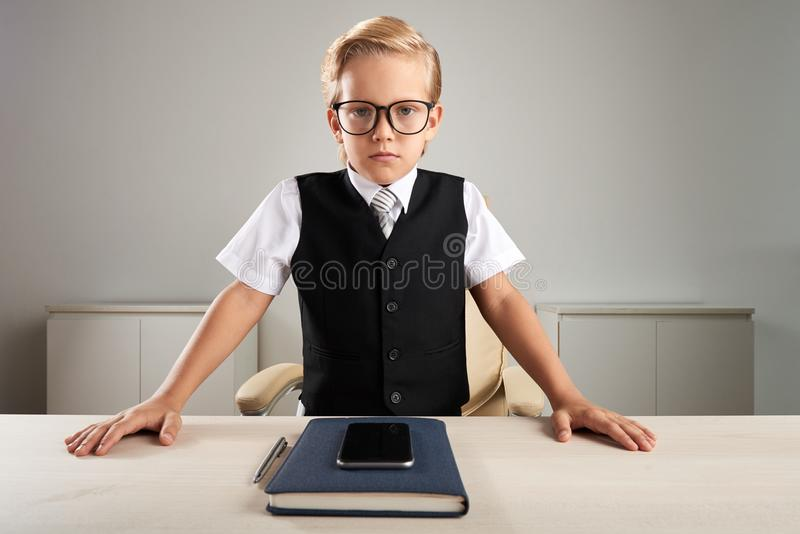 Little CEO. Serious little CEO standing at his workplace stock photos