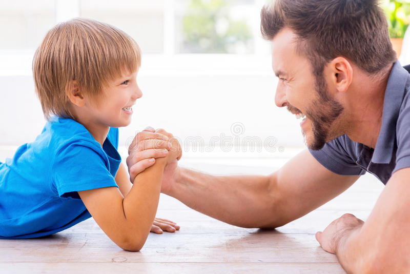 Little champion in arm wrestling. Side view of happy father and son competing in arm wrestling while both lying on the hardwood floor stock images