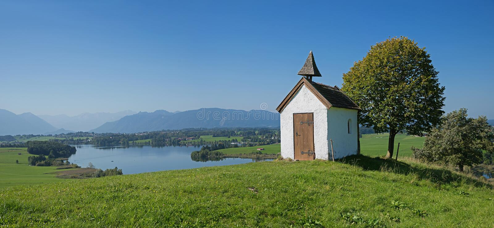 little chapel in idyllic bavarian landscape with lake view riegsee stock image
