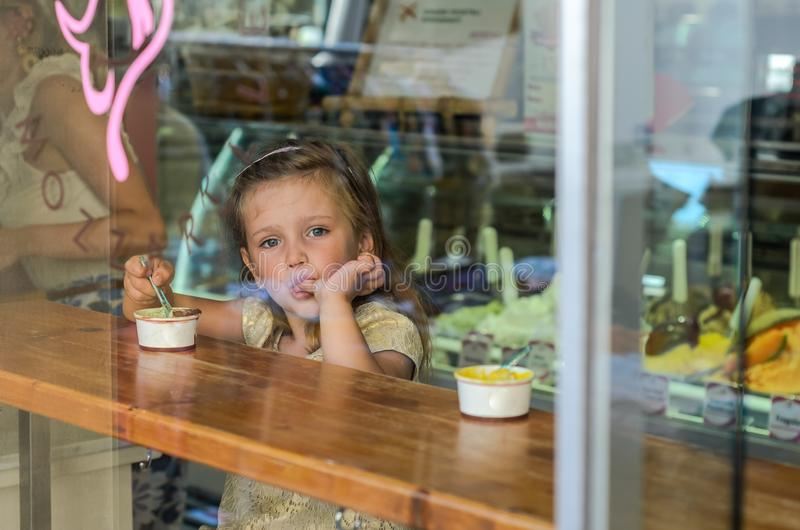 ROMA, ITALY - AUGUST 2018: Little charming baby girl eating ice cream in a cafe, view through the window stock photo