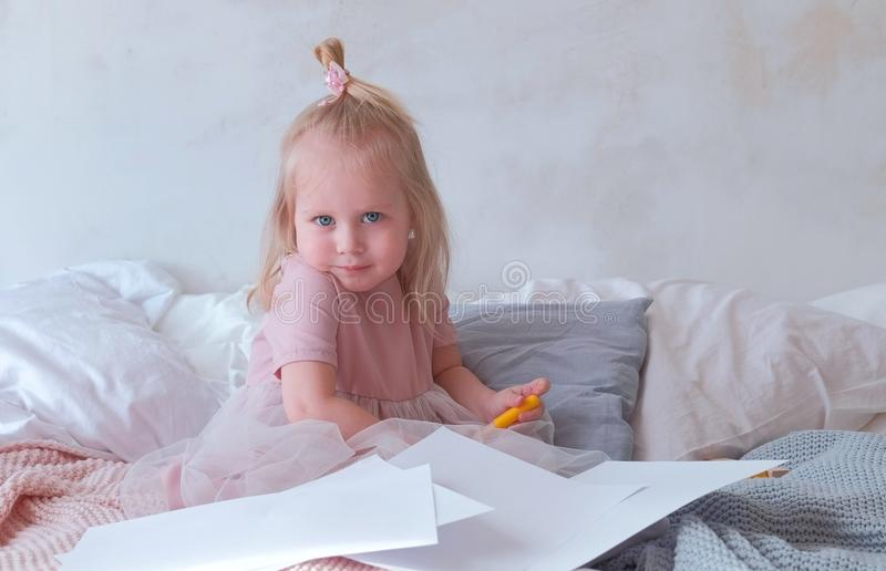 Little charming blond girl in pink dress holding a felt-pens and sitting on bed among paper. stock image