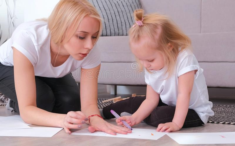 Little charming blond girl refuses to paint felt-pen with her attractive mom sitting near the sofa. royalty free stock photo