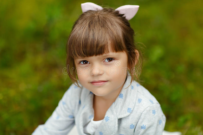 Little charming girl with brown eyes on the background of the forest in the summer seriously looking, close-up stock photo