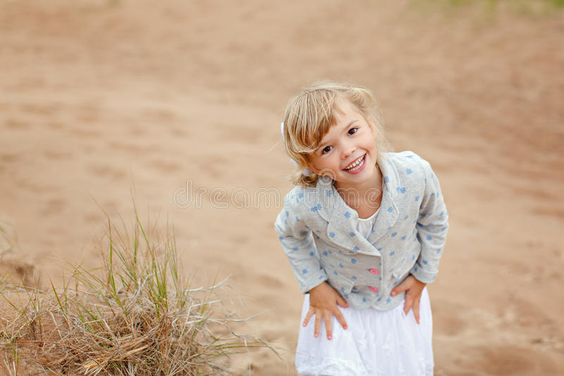 Little charming girl with brown eyes on a background of sand smiles summer and laughs stock image