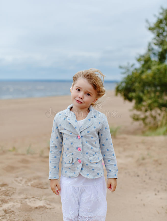 Little charming girl with brown eyes on the background of the se stock photos
