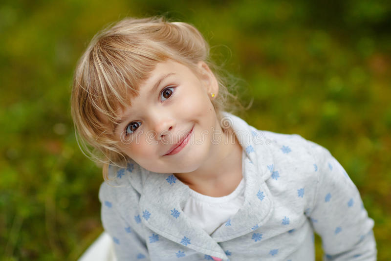 Little charming girl with brown eyes on the background of summer stock photos