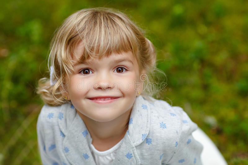 Little charming girl with brown eyes on the background of summer stock image