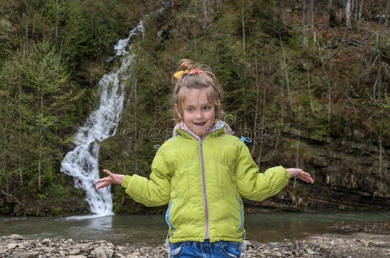Little charming girl child on the background of a mountain waterfall.  stock photo