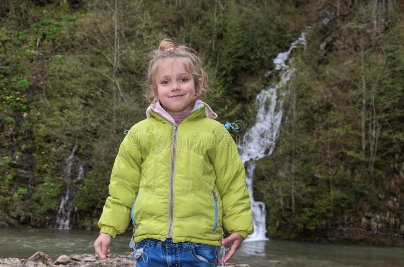 Little charming girl child on the background of a mountain waterfall.  royalty free stock photo