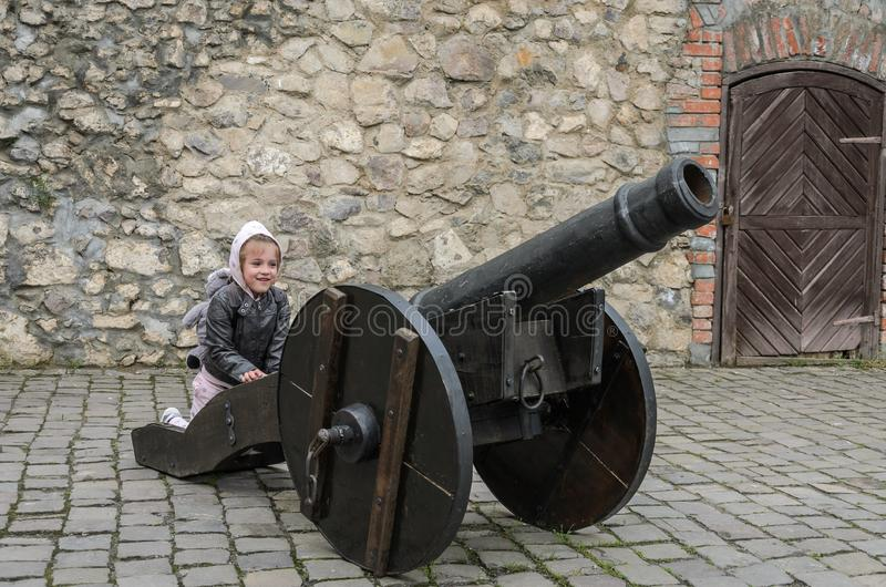 Little charming girl child at the historic ancient cannon in the old castle of the fortress royalty free stock photos