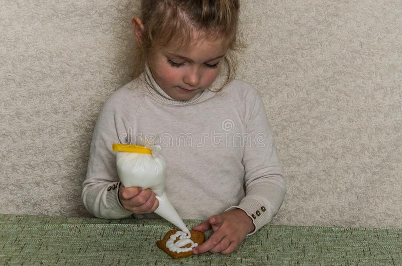 Little charming girl decorates New Year`s gingerbread with white sugar icing.  royalty free stock photos