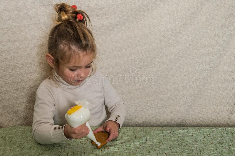 Little charming girl decorates New Year`s gingerbread with white sugar icing.  stock photography