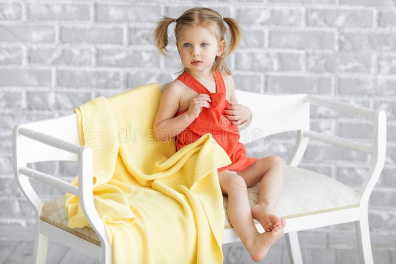 Little charming girl in a red dress is sitting on a white sofa. royalty free stock photos
