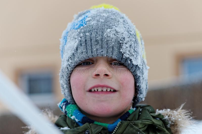 Little cheerful boy playing with snow stock image