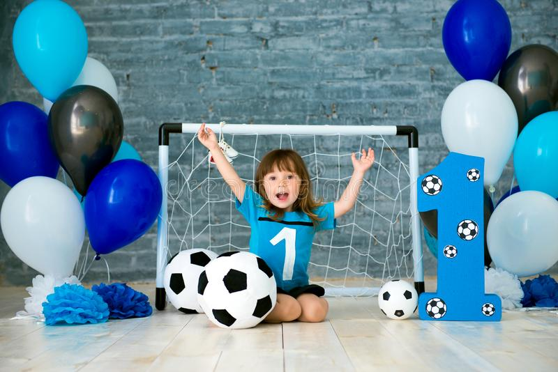 Little cheerful child dressed in sports clothes sitting on the floor near a football goal, looking at a big soccer ball royalty free stock image
