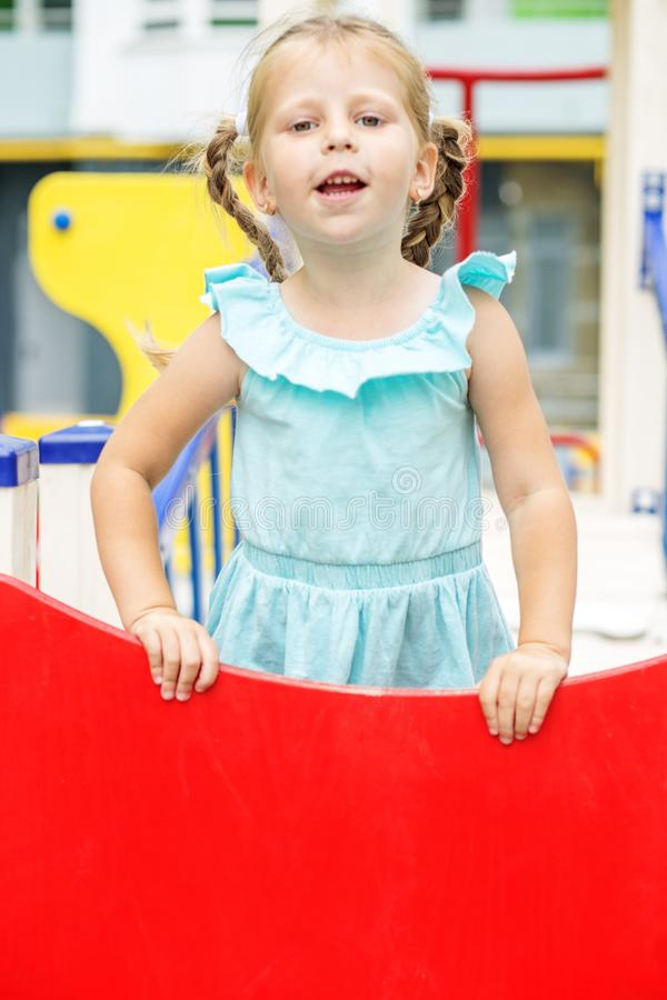 Little cheerful child plays on the playground. The concept of childhood, lifestyle, upbringing, kindergarten. Little cheerful child plays on the playground. The stock photography